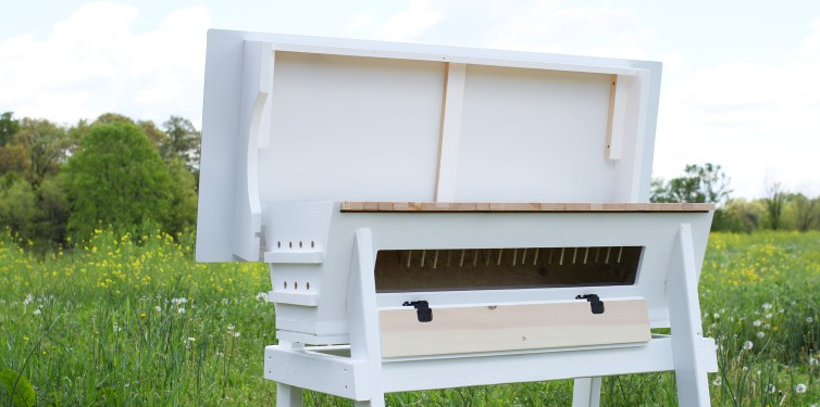 The hinged roof on our top bar hive design conveniently stays up